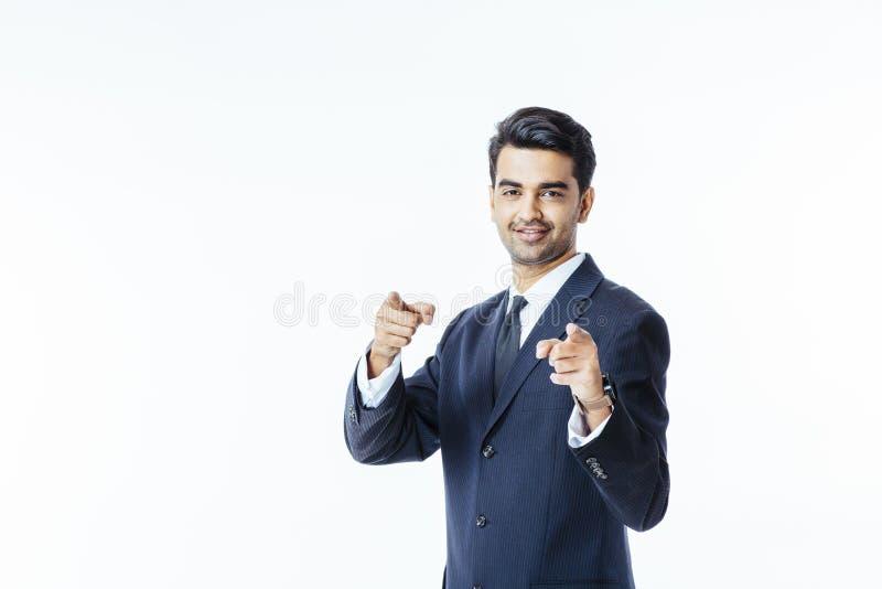Stilig lyckad affärsman i svart dräkt och band som pekar på kameran med två fingrar royaltyfri bild