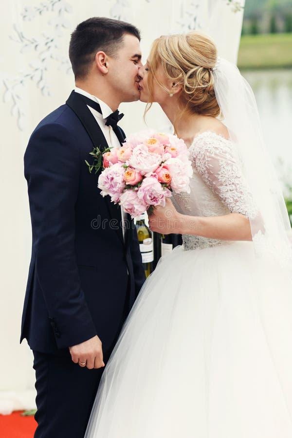 Stilig lycklig brudgum och härlig blond brud i vit klänning K royaltyfri bild