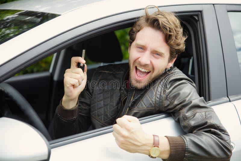 Stilig lycklig man i bil som ler hållande tangent arkivfoton