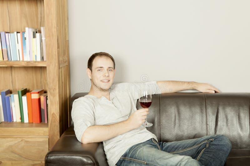 Stilig lycklig man som kopplar av med ett exponeringsglas av vin arkivfoton