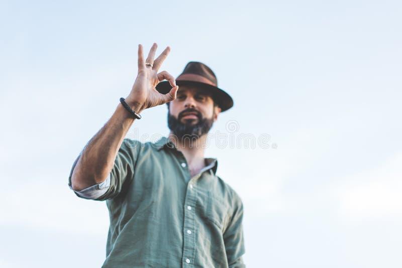 Stilig lycklig skäggig hipster som ser kameran till och med hans fingrar i ok gest Hållande ögonen på begrepp för folk arkivfoto
