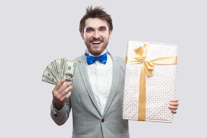 Stilig lycklig ung skäggig man, i grå dräkt och blått flugaanseende och att rymma gåvaasken med den gula pilbågen och många kassa royaltyfri foto