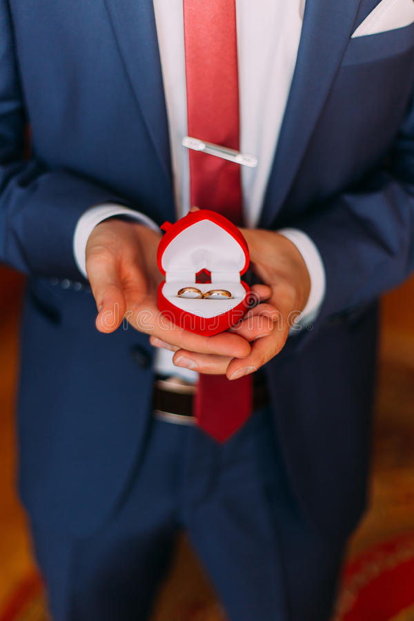 Stilig lyx klädd man i stilfull blå hållande röd hjärta-formad ask med vigselringar Närbild arkivbilder