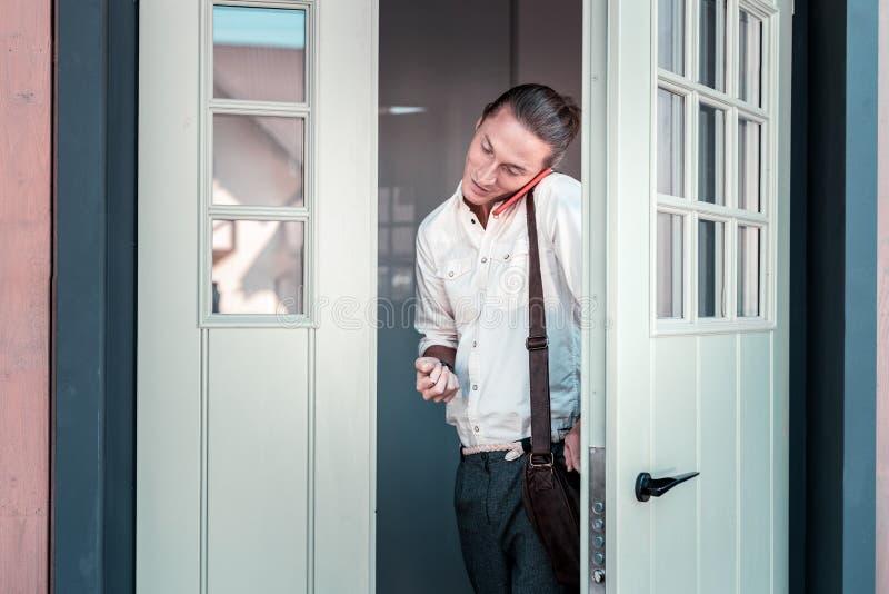 Stilig mörker-haired affärsman som lämnar den hem- överskriften för att arbeta royaltyfri foto
