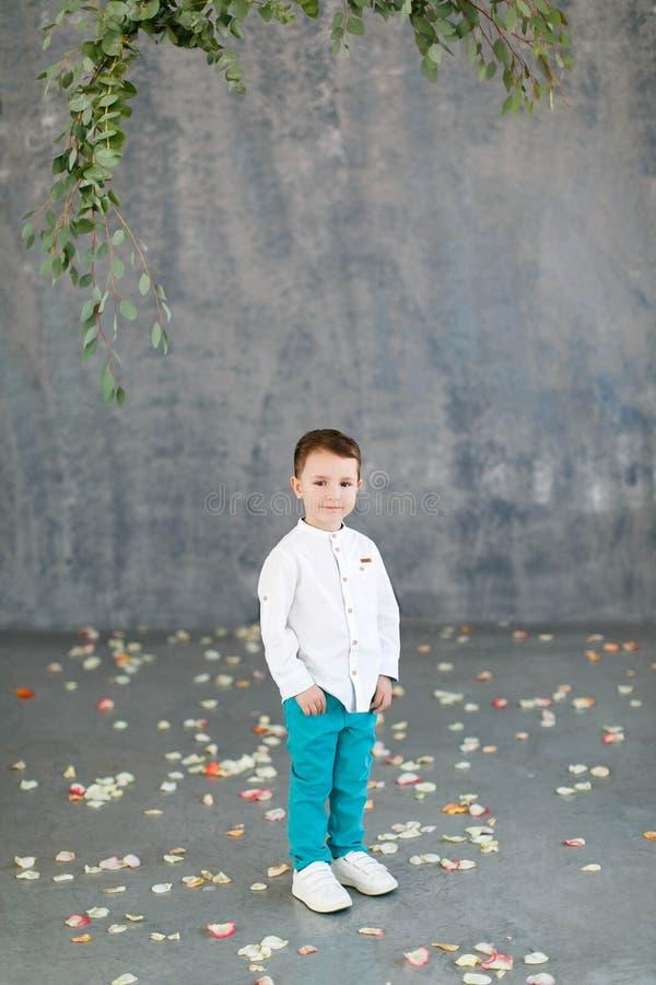 Stilig mörker-haired pojke i en vit skjorta, turkosflåsanden och vita gymnastikskor på en grå färg fotografering för bildbyråer
