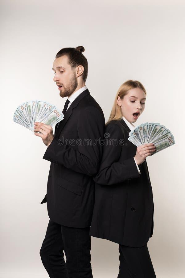 Stilig man för två anställda och härlig blond kvinna i svarta dräkter som tillbaka står för att dra tillbaka med pengar i händer royaltyfri bild