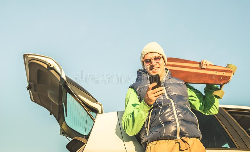 Stilig man för ung hipster med musik för smart telefon för mobil lyssnande på bilvägturen royaltyfri foto