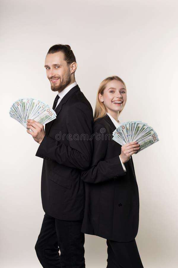 Stilig man för unga familjpar och hans härliga blonda fru, både i svarta dräkter som tillbaka står för att dra tillbaka med penga royaltyfria foton