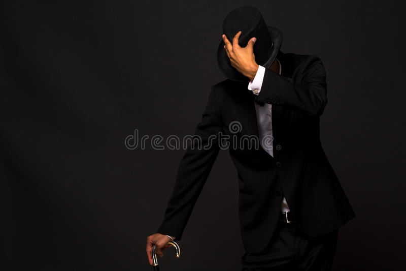 Stilig man i den bästa hatten som poserar med rottingen royaltyfri bild