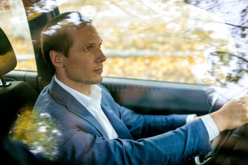 Stilig man i dräkten som sitter i bil bak hjulet royaltyfri bild