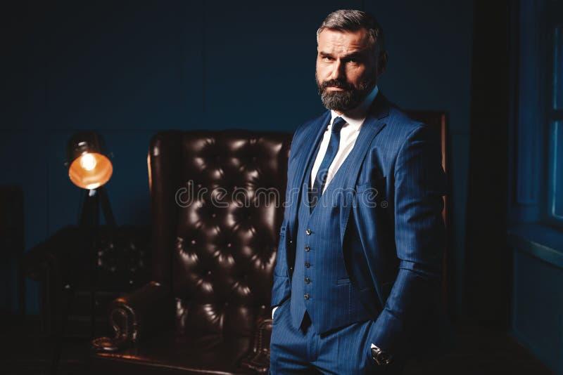 Stilig man i elegant dräkt i lyxig inre Closeupstående av den trendiga säkra mannen i lyxig lägenhet royaltyfri foto
