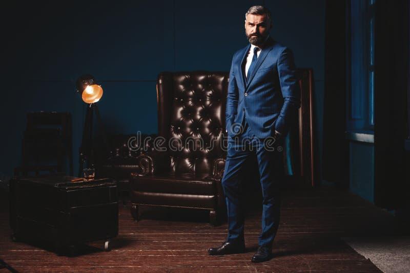 Stilig man i elegant dräkt i lyxig inre Closeupstående av den trendiga säkra mannen i lyxig lägenhet arkivfoto