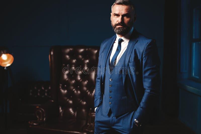Stilig man i elegant dräkt i lyxig inre Closeupstående av den trendiga säkra mannen i lyxig lägenhet arkivbild