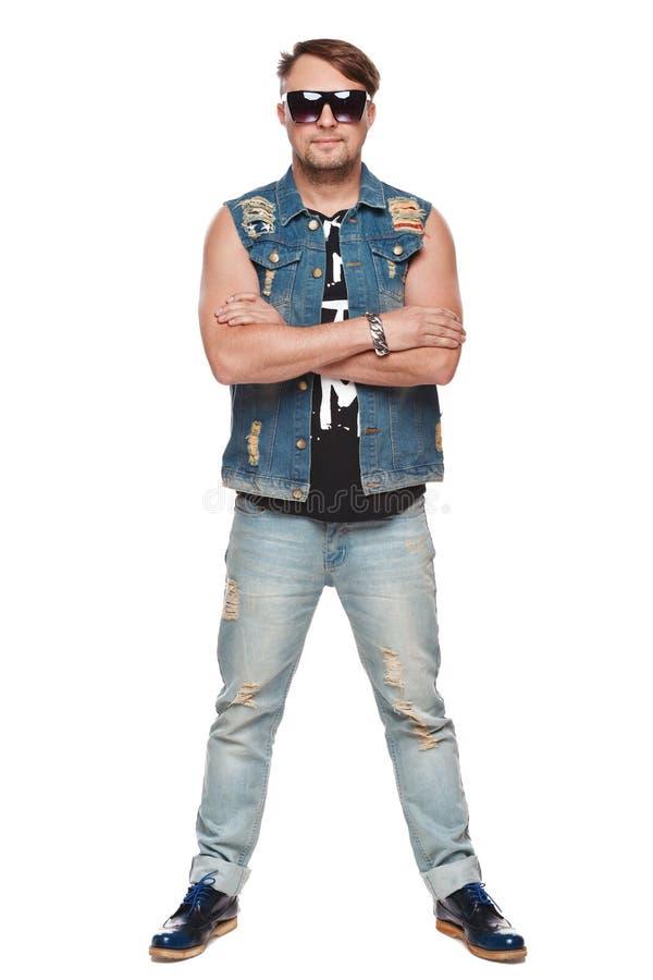 Stilig man i jeans och solglasögon som poserar den oavkortade längden, modeman Isolerat över vitbakgrund royaltyfri bild