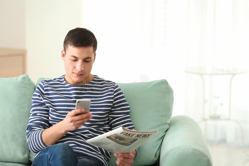 Stilig man med mobiltelefonen och tidningen som hemma sitter på soffan royaltyfri foto