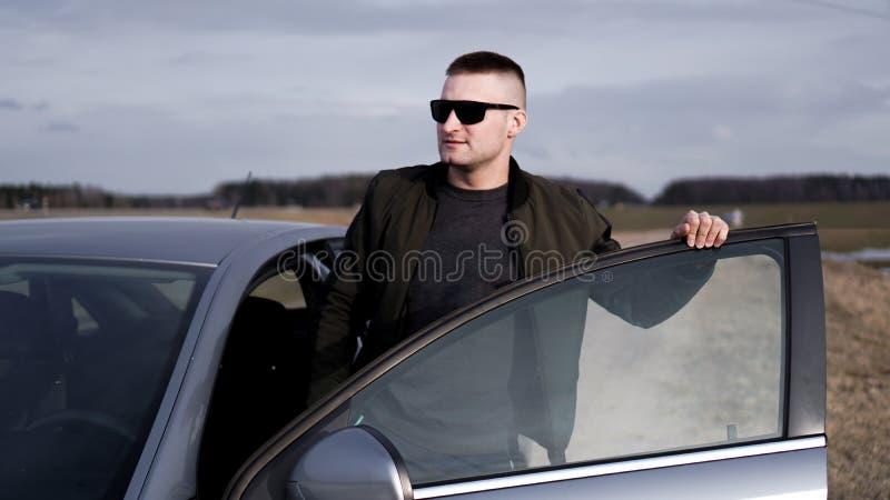 Stilig man nära bilen stående för man för glass livstid för konjakaffärscigarr lyxig royaltyfri foto