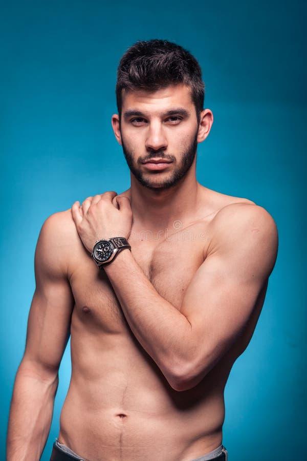 Stilig man och att posera, shirtless kropp, blå bakgrund arkivfoto