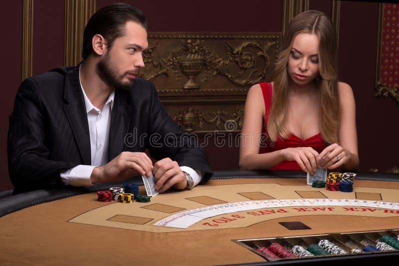 Stilig man och härlig kvinna i kasino arkivfoto