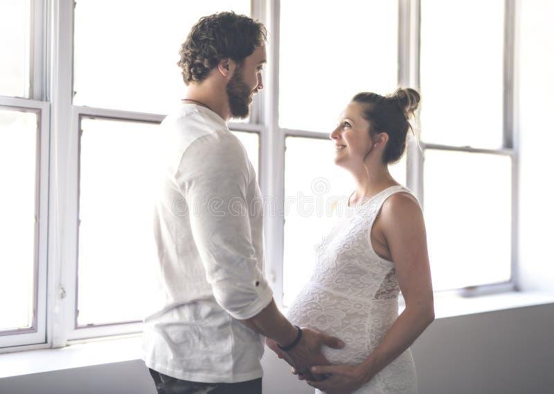 Stilig man och hans härliga gravida fruanseende nära fönstret hemma royaltyfri fotografi