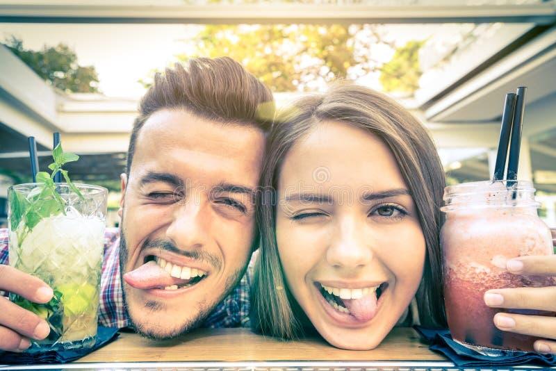 Stilig man och ung lycklig kvinna som har gyckel på coctailstången royaltyfri foto