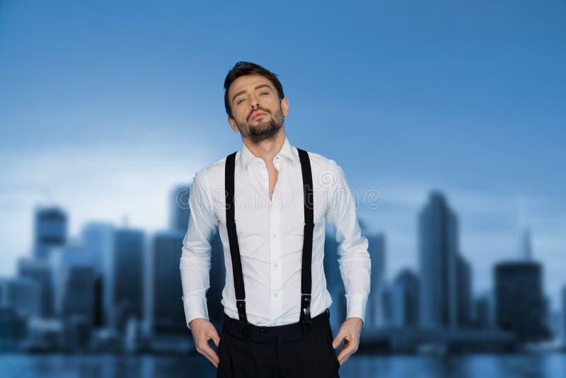 Stilig man på den blå bärande vit skjortan och hänglsen arkivfoto