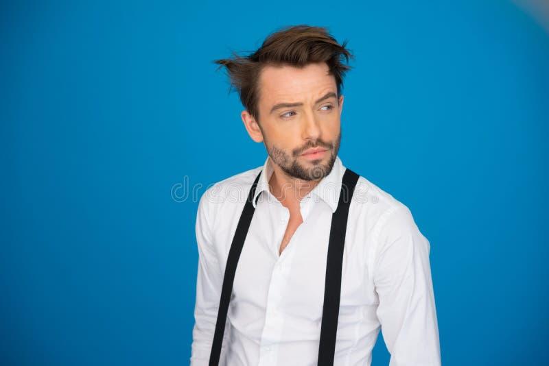 Stilig man på den blå bärande vit skjortan och hänglsen fotografering för bildbyråer