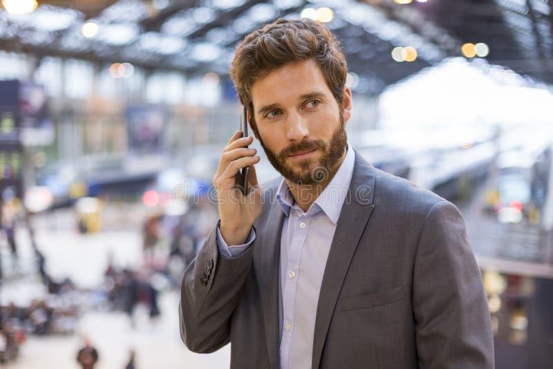 Stilig man på mobiltelefonen i korridorstation arkivfoton