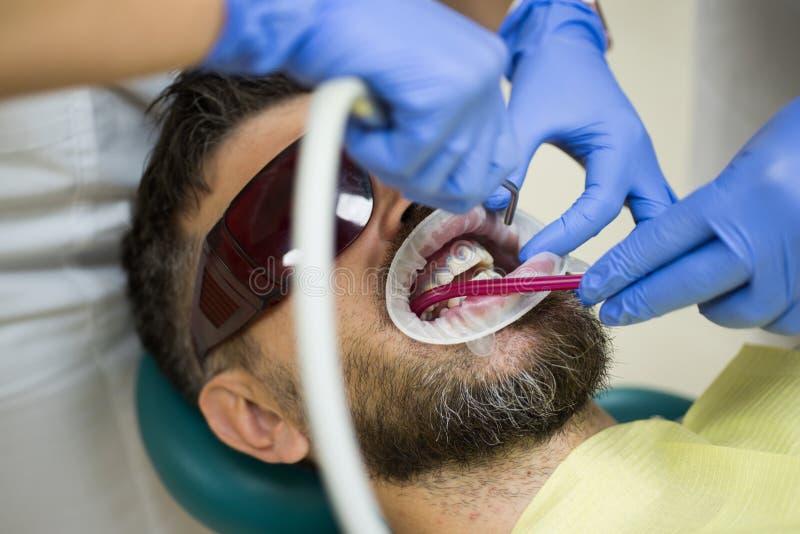 Stilig man på tandläkares kontor Kvinnlig tandläkare som kontrollerar tålmodiga tänder med spegeln i modern tand- klinik Undersök arkivbilder