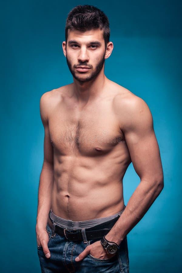 Stilig man som är shirtless, händer i fack, blå bakgrund royaltyfri fotografi