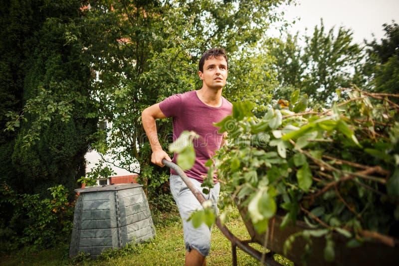 Stilig man som arbeta i trädgården i hans trädgård royaltyfria foton