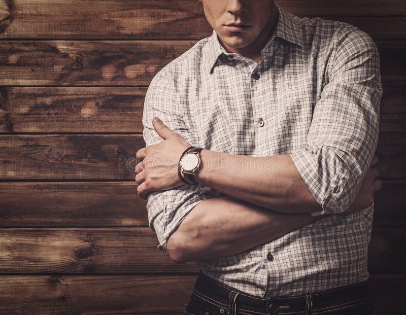 Stilig man som bär den rutiga skjortan i trähusinre royaltyfria bilder