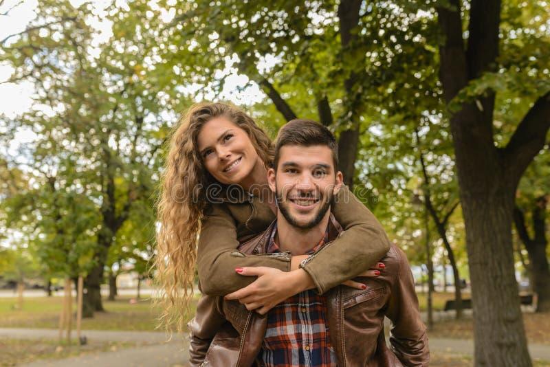 Stilig man som bär hans attraktiva flickvän på baksidan arkivbilder