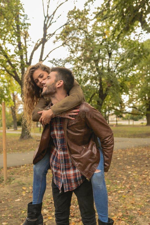 Stilig man som bär hans attraktiva flickvän på baksidan royaltyfria foton