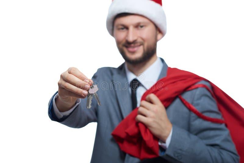 Stilig man som bär som santa som ger tangent av bilen eller huset royaltyfri fotografi