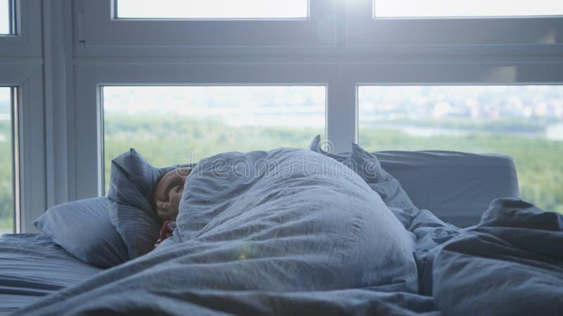 Stilig man som Cozily sover i säng vid fönstret royaltyfri fotografi