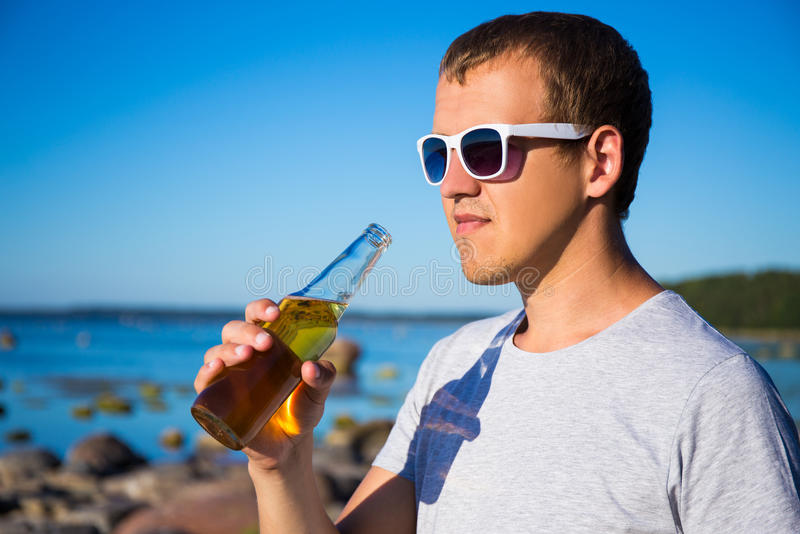 Stilig man som dricker öl på stranden arkivfoton