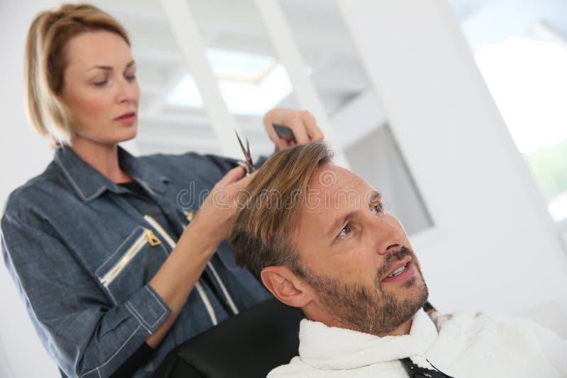 Stilig man som får frisyr på frisören royaltyfria bilder
