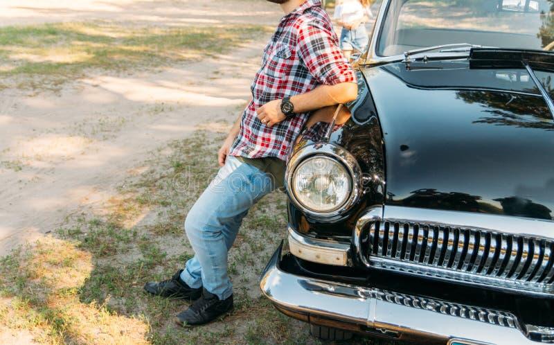 Stilig man som framme står av bilen på hans hand är en svart klocka Vänta på ett möte vila förväntan av ögonblicket stands arkivfoto