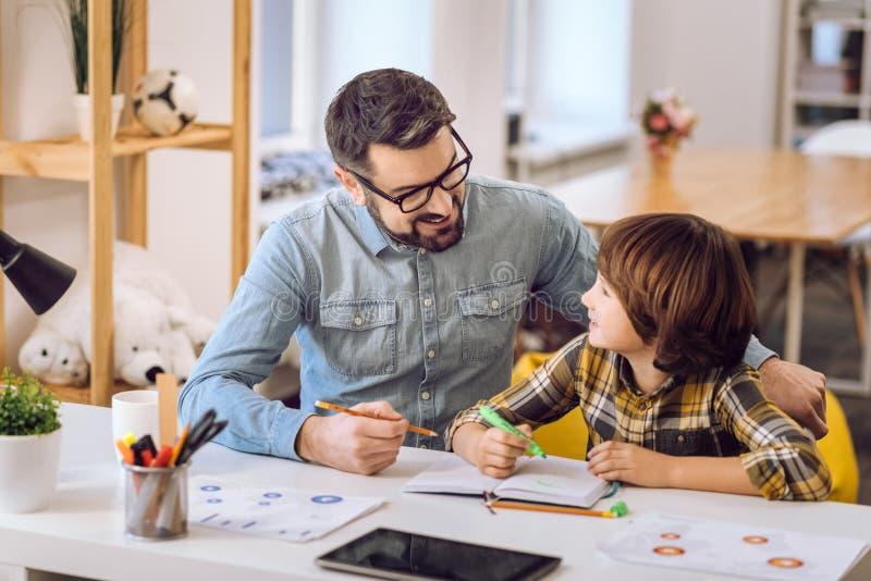 Stilig man som gör uppgifter med hans son arkivfoto