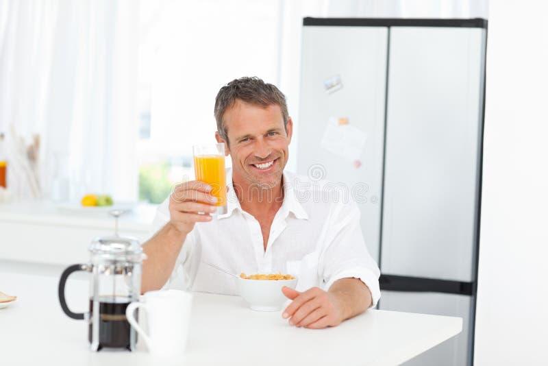 Stilig man som har hans frukost i kök 图库摄影