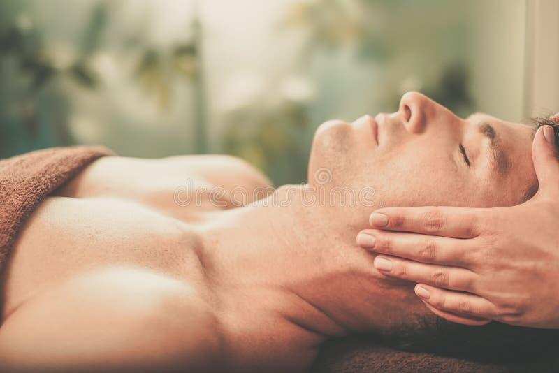 Stilig man som har massage i brunnsortsalong royaltyfria bilder