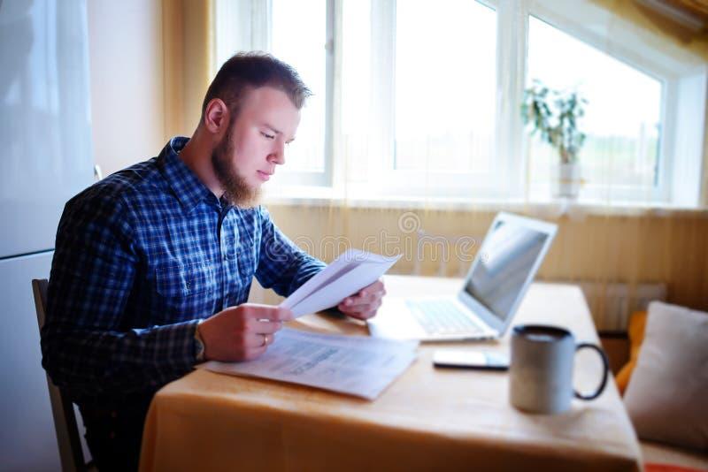 Stilig man som hemma gör någon skrivbordsarbete royaltyfria bilder