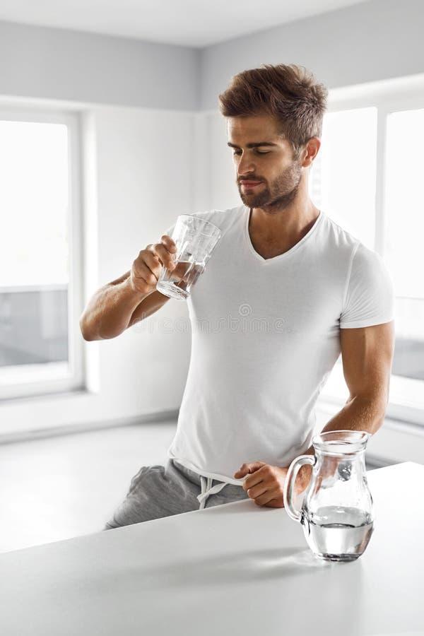 Stilig man som inomhus dricker exponeringsglas av sötvatten i morgon royaltyfri bild