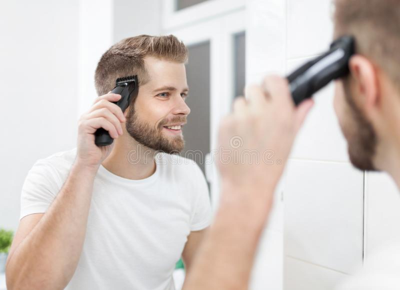 Stilig man som klipper hans eget hår med en clipper royaltyfri foto