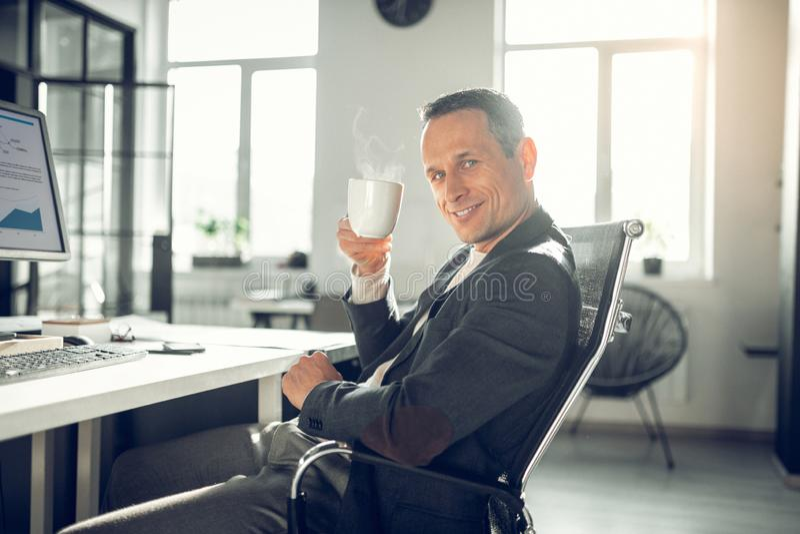 Stilig man som ler, medan dricka bra kaffe i kontoret arkivbild