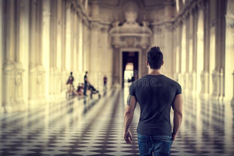 Stilig man som omkring ser inom ett museum arkivfoto