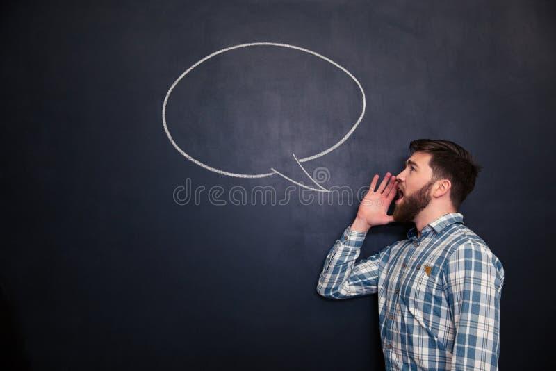 Stilig man som ropar mot svart tavlabakgrund med den utdragna anförandebubblan royaltyfria foton