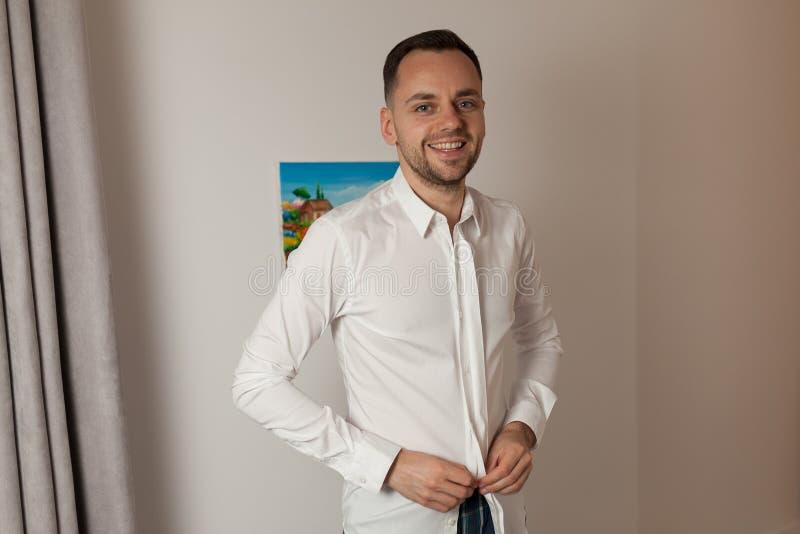 Stilig man som sätter på skjortan som står det near fönstret på hans rum I arkivfoto
