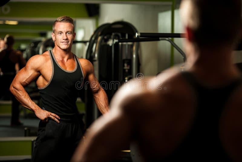 Stilig man som ser i spegel efter kroppbyggnadsgenomkörare i fi arkivfoto