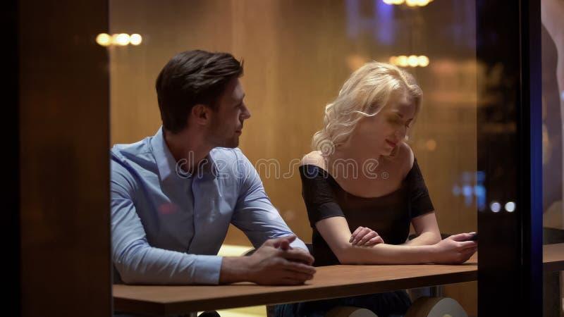 Stilig man som sitter i restaurang och flörtar med den blyga kvinnan, förhållande royaltyfri foto
